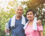Portrait of Asian Senior couple in blue and pink shirt smiling and standing before exercising at park outdoor. Good health.