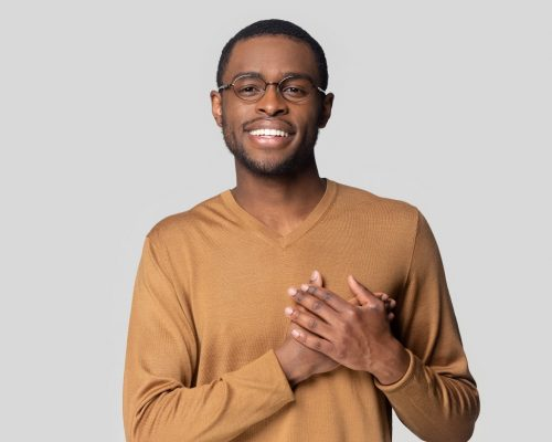 Head shot portrait close up smiling African American man in glasses keeping hands on chest, looking at camera, grateful young male feeling gratitude, appreciation, isolated on grey background