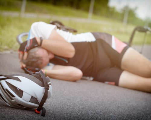 Cyclist lying on the road and holding his head, helmet in foreground