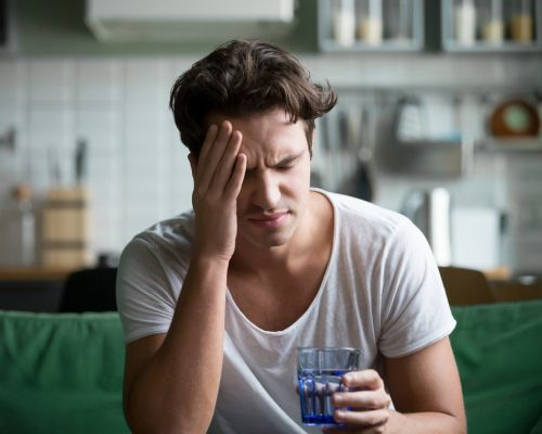 Young man suffering from strong headache or migraine sitting with glass of water in the kitchen, millennial guy feeling intoxication and pain touching aching head, morning after hangover concept