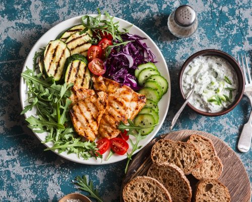 Grilled chicken breast, zucchini and garden vegetable power bowl. Healthy diet food concept, top view