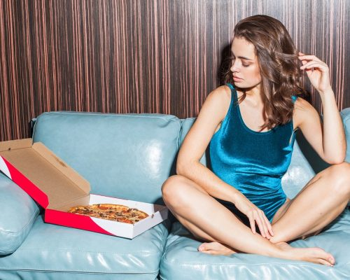sexy woman in swimwear sitting on sofa with pizza at home interior