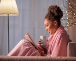 Side view of happy young woman reading book with interest. She is holding cup of coffee and smiling. Lady is sitting on sofa covered by blanket. Warm and comfort concept