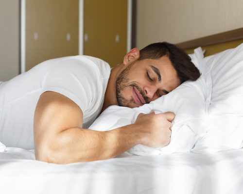 Young eastern man peacefully sleeping in his bed, panorama with copy space