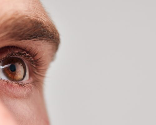 Extreme Close Up Of Eye Of Man Against White Studio Background
