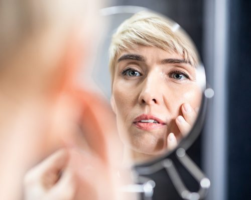 Skin Aging. Pretty Mature Woman Looking In Mirror Touching Face Standing In Bathroom At Home. Selective Focus