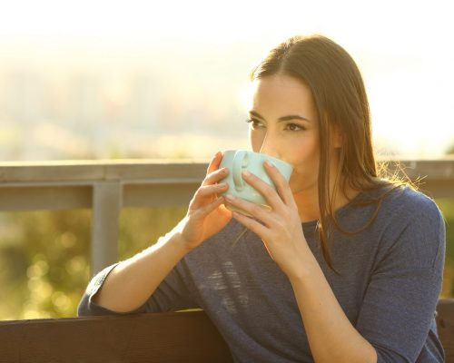 Woman drinking coffee in a park at sunset