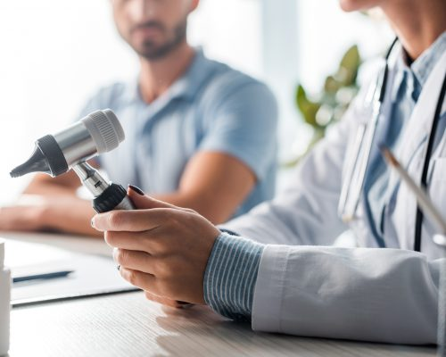 cropped view of doctor holding otoscope near man in clinic