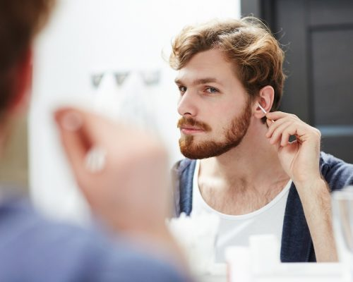 Young man cleaning his ears in front of mirror