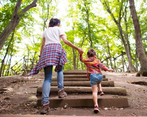 Mother and daughter are up the stairs in the woods hand in hand