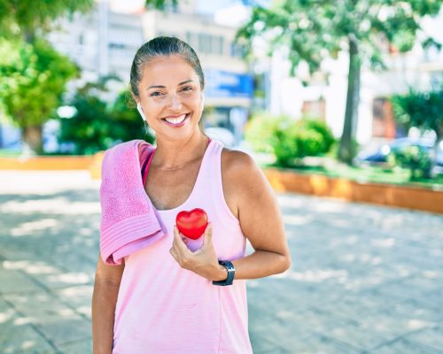 Middle age sportswoman asking for health care holding heart at the park
