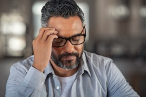 Frustrated middle aged man with hand on head sitting on couch at home. Close up face of stressed indian businessman wearing eyeglasses with eyes closed. Worried middle easter business man with terrible migraine, overload and overworked concept.