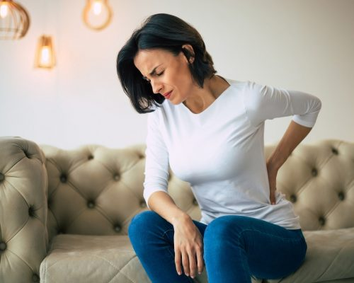 A hurting woman, who is sitting on a couch and holding her lower back with her left hand.