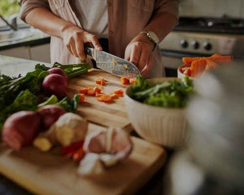 Female hands cutting vegetables on cuttiing board - woman preparing a healthy meal to boost the immune system