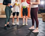 Cropped photo of four slim young women in sporty gear holding resistance bands at the gym