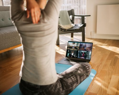 Fitness coach teaching yoga online to group of people. Yoga trainer demonstrating yoga poses to students via video conference.