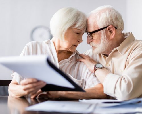 Selective focus of man embracing senior wife near documents on table