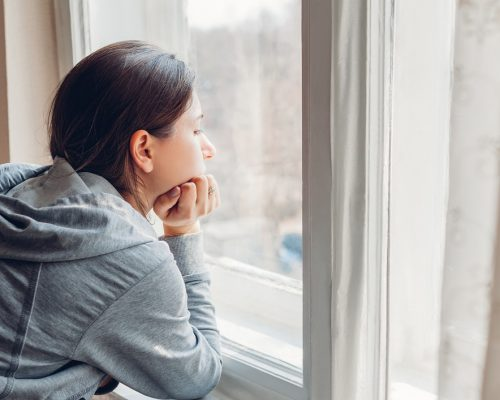 Isolation at home during coronavirus covid-19 pandemic. Woman looking at window. Sad girl stays safe at home on quarantine