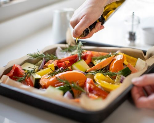 Close Up Of Seasoning Tray Of Vegetables For Roasting With Olive Oil Ready For Vegan Meal
