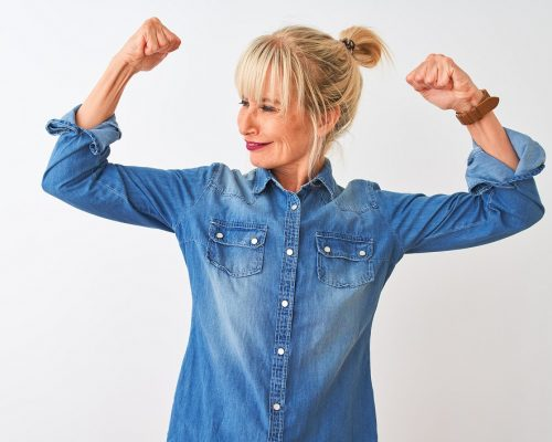 Middle age woman wearing casual denim shirt standing over isolated white background showing arms muscles smiling proud. Fitness concept.