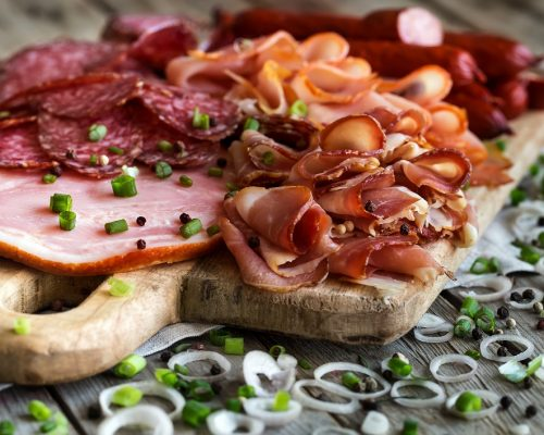 Mix of meat appetizers - salami, ham, smoked turkey, sausages and prosciutto - on rustic wooden background