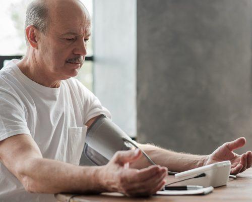 Senior man using a home blood pressure machine to check his vital statistics sitting at the living room
