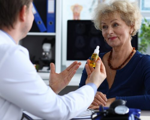 Portrait of aged senior female consulting with doctor. Therapeutic in medical gown advising cannabinoid oil to patient. Practitioner holding bottle with cannabis leaf sign