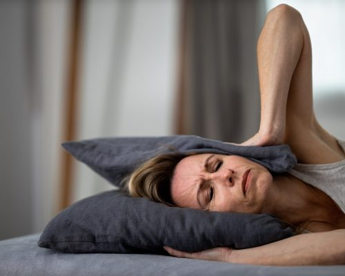 Sleepless lady covering ears with pillow. Noisy neighbors, tinnitus, insomnia or stress concept. Tired woman can't sleep. Awake in bed after coming home from her shifh, work. Noise from party next door.