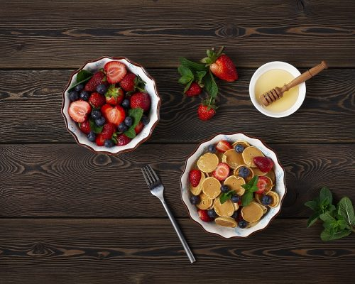 food Dutch mini pancakes, homemade, with strawberries and blueberries, breakfast , on a wooden table, top view, no people, horizontal,