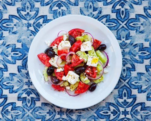 Greek salad. Fresh vegetables, feta cheese and black olives. Top view.