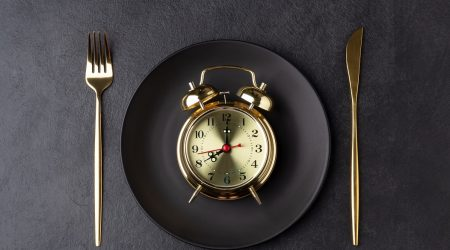 Golden alarm clock on a black plate with a golden knife and fork. Intermittent fasting concept. Horizontal orientation, top view.