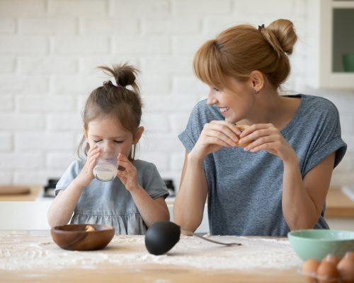 Happy young Caucasian mother and little preschooler daughter sit at kitchen table baking eating cookies together, smiling mom have fun with small girl child teach bakery enjoy family weekend at home