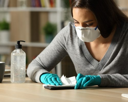 Woman with gloves and protective mask disinfecting smart phone from coronavirus sitting on a desk at night at home