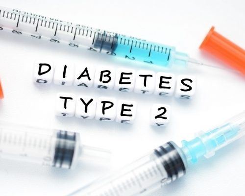 Type 2 diabetes text spelled with plastic letter beads placed next to an insulin syringe