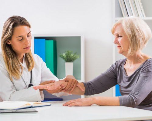 Female doctor examines her senior patient's wrist in office.