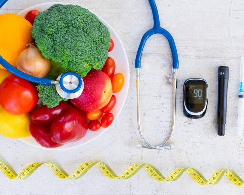 Diabetes healthy diet concept, raw vegetables and fruits with blood glucose meter and insulin syringe