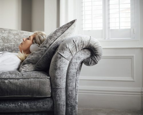 Mature woman lying on her sofa, enjoying listening to some music through headphones.