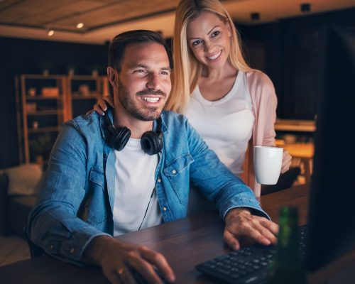 Beautiful women holding cup of coffee, giving it to her man who is working on his computer at night