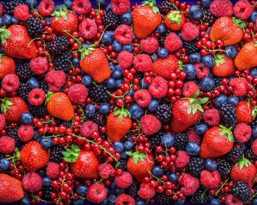 Berries overhead closeup colorful assorted mix of strawbwerry, blueberry, raspberry, blackberry, red curant in studio on dark background