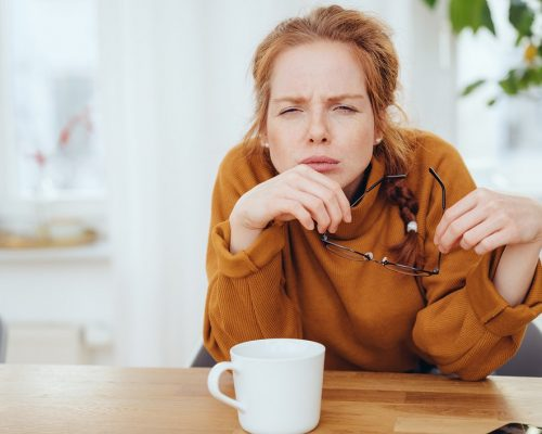 Girl with poor eyesight squinting without glasses, sitting at the table indoors with a cup of tea. Trying to look at something, holding glasses in her hands. Half-length portrait with copy space