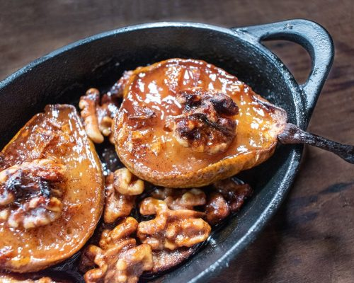 small cast iron dish of roasted pear halves with walnuts and sugar glaze top view
