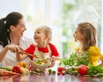 Healthy food at home. Happy family in the kitchen. Mother and children daughters are preparing the vegetables.