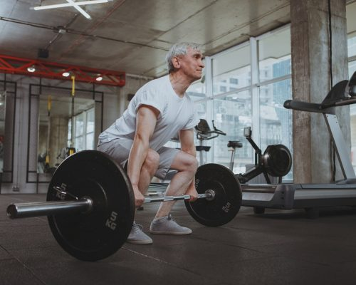 Full length shot of a senior sportsman doing deadlift at the gym. Healthy strong elderly man working out with heavy barbell at sport studio. Bodybuilding, health, active lifestyle concept
