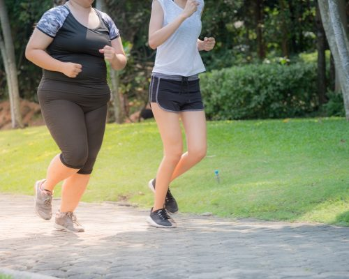 blurred motion of two women exercising by jogging in the park, they are running for health and fitness.