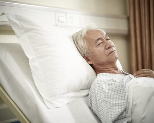 asian elderly male patient lying in bed sleeping in hospital ward or assisted living facility