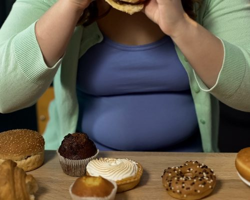 Overweight woman consuming too much bakery, eating stress with unhealthy sweets