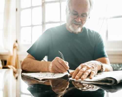 cropped image of senior men writing crossword on newspaper