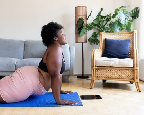 Woman doing yoga exercise on mat at home. Healthy african woman practicing cobra yoga pose. Exercising at home during pandemic.