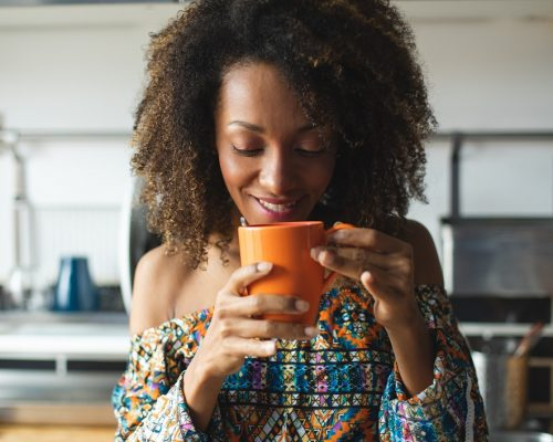 Casual young black woman taking a relaxing cup of coffeee in the kitchen at home. Afro hairstyle model.
