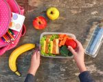 Sandwiches, fruits and vegetables in food box, backpack on old wooden background. Concept of child eating at school. Top view. Flat lay.